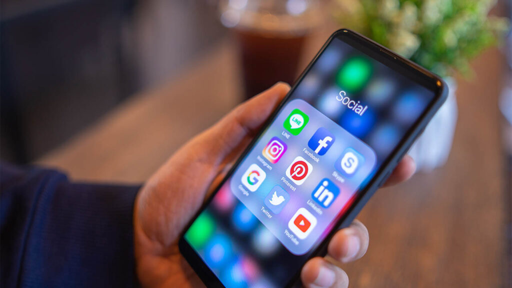 Holding a smartphone with social media apps open